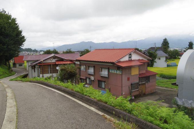 駅前風景。水田と民家・民宿が ...